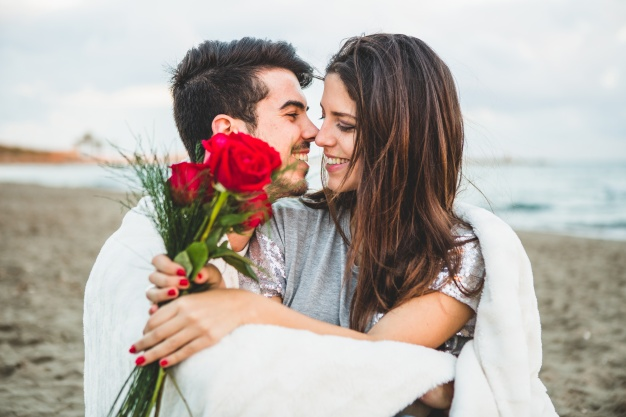 loving-couple-sitting-beach-with-bouquet-roses_23-2147595917